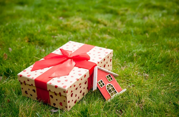 Holiday gift box and little house toy on green grass