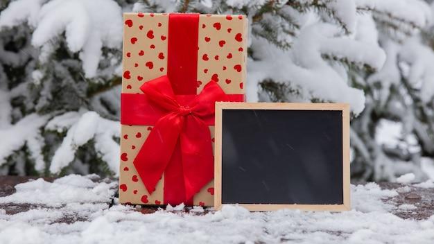 Праздничная подарочная коробка с сердечками и доской на деревянном столе в снегу