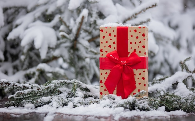 Holiday gift box with heart shapes on wooden table in snow