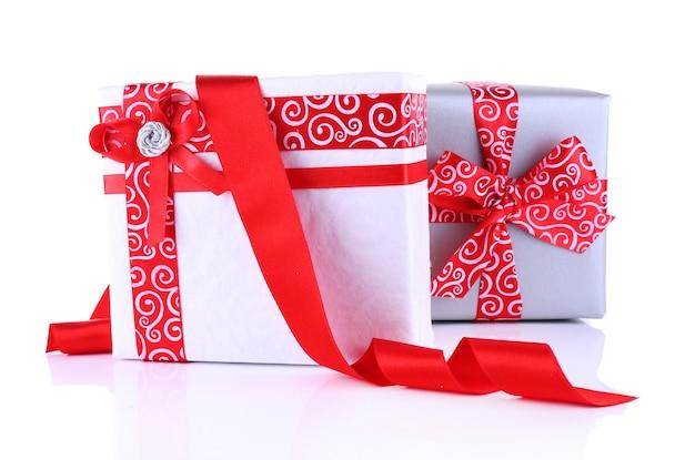 白で隔離の赤いリボンで飾られたホリデーギフトボックス
