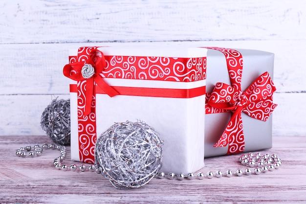 Праздничные подарочные коробки, украшенные красной лентой на столе на фоне деревянной стены