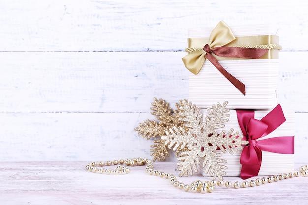 Праздничные подарочные коробки, украшенные бордовой лентой на столе на фоне деревянной стены