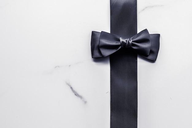 ホリデーギフトの装飾と販売促進のコンセプト黒のシルクリボンと大理石の背景の弓...