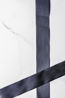 Праздничное оформление подарков и концепция продвижения по продаже черная шелковая лента и бант на мраморном фоне flatlay