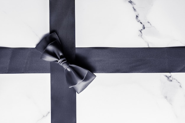 Holiday gift decoration and sale promotion concept  black silk ribbon and bow on marble background f...