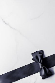 Holiday gift decoration and sale promotion concept  black silk ribbon and bow on marble background flatlay