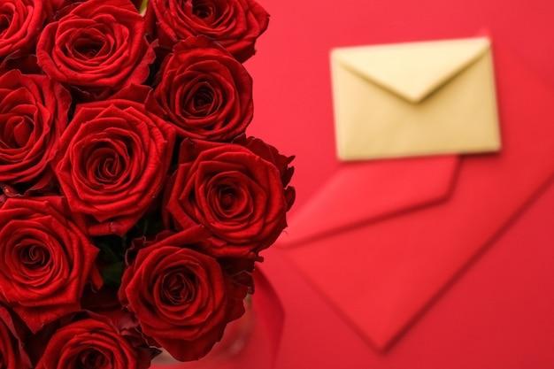 Праздничный подарок цветы flatlay и концепция счастливых отношений любовное письмо и служба доставки цветов на день святого валентина роскошный букет из красных роз и карточных конвертов на красном фоне