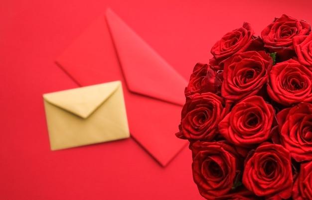 ホリデーギフト花フラットレイと幸せな関係のコンセプトバレンタインデーのラブレターと花の配達サービス赤いバラと赤い背景のカード封筒の豪華な花束