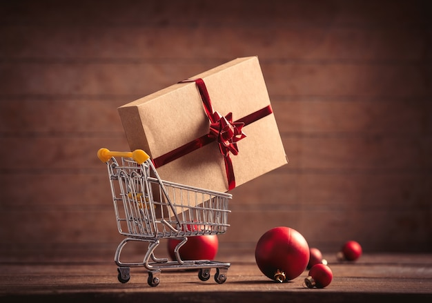 Holiday gift in shopping cart on wooden table and background