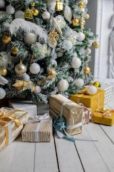 크리스마스 트리 아래 크리스마스 선물은 꼬기로 싸서 화환 조명과 장난감으로 장식 된 포장지입니다.