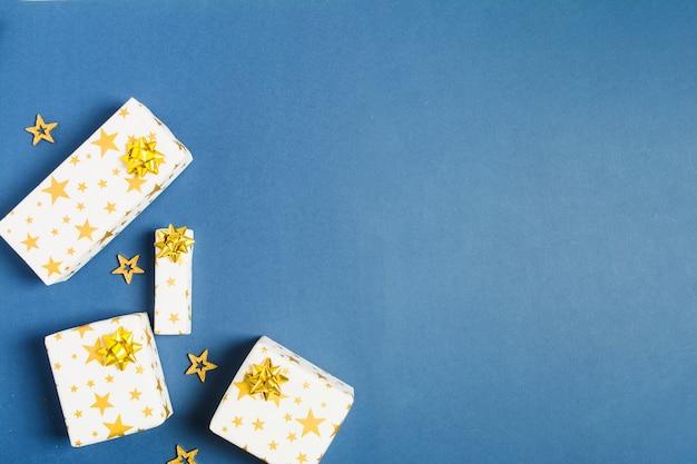 Праздничный подарок оберточной бумагой со звездами и золотыми бантами с конфетти