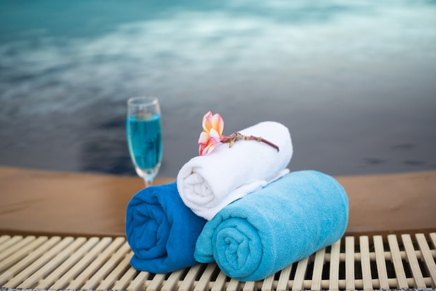 Holiday glass of white wine and towel by swimming pool.