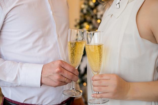 シャンパンのグラスと新郎新婦の人々の手で新年holiday.glassesを見越して手にシャンパンのグラスとエレガントな休日の服の男女。パーティーまたは