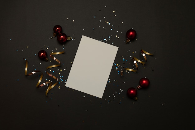 Holiday golden decorations and white notebook on black background.