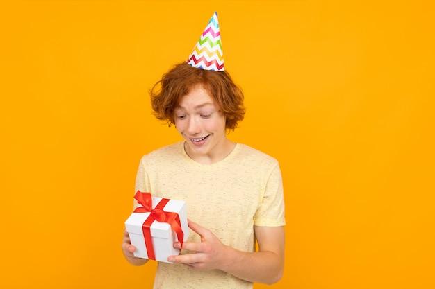 休日 。オレンジ色の彼の手でギフトを持つ幸せな驚いた赤毛の少年