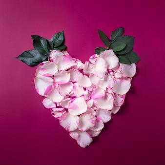 Праздничный венок в форме сердца из лепестков роз на красном фоне, поздравительная открытка на день святого валентина или свадьбы, вид сверху
