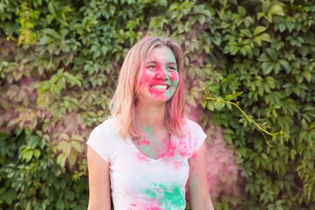 휴일, holi 및 사람들 개념-그녀의 셔츠에 녹색 가루와 함께 포즈 아름 다운 젊은 여자