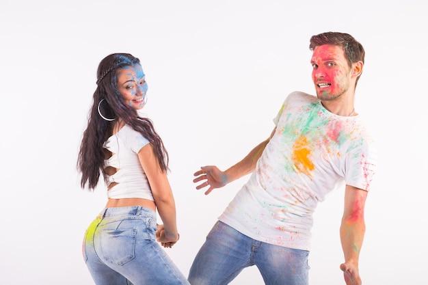 휴일, holi 및 사람들이 개념-행복 한 커플 재미 흰색 표면에 페인트로 덮여