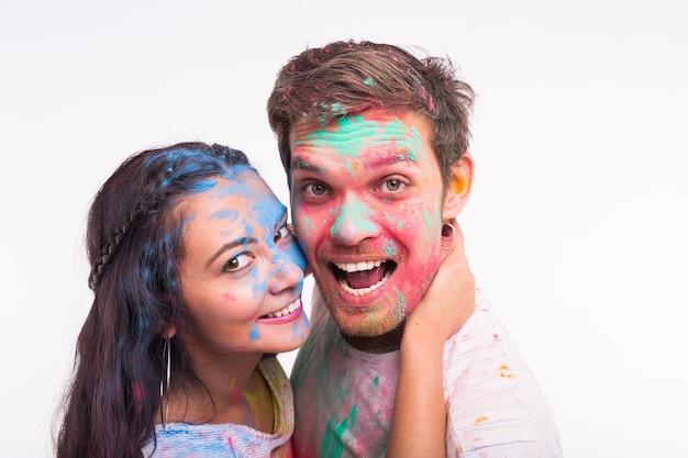 휴일, holi 및 사람들 개념-재미 있은 여자와 남자가 흰색 표면에 얼굴에 여러 가지 빛깔의 가루와 함께 포즈 미소
