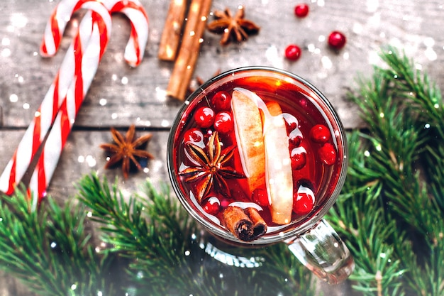 Holiday hot drink. mulled wine in glass with spices and apple on wooden table background.