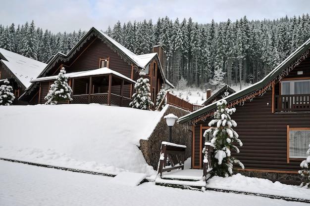 冬の新雪に覆われた山のホリデーリゾートの別荘。木製のコテージ。
