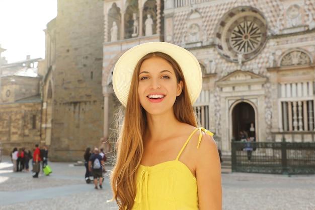 Отдых в италии. портрет молодой женщины в шляпе и желтом платье на площади пьяцца дель дуомо в городе бергамо, ломбардия, италия.