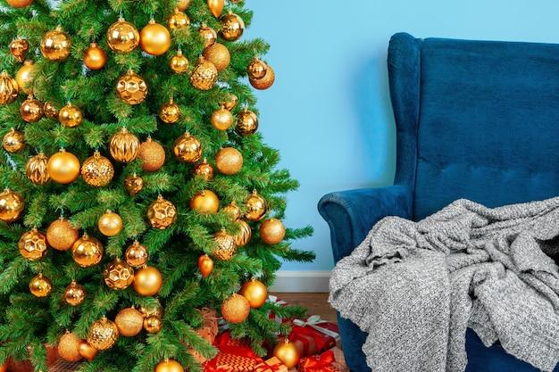휴일 인테리어는 파란색 안락의자가 있는 아름다운 장식된 크리스마스 트리