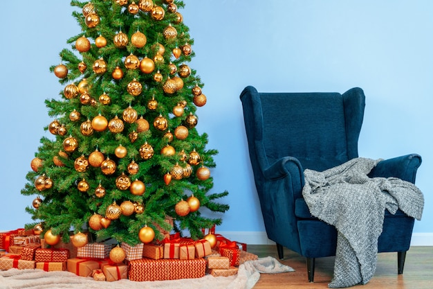 Holiday interior. beautiful decorated christmas tree with blue armchair