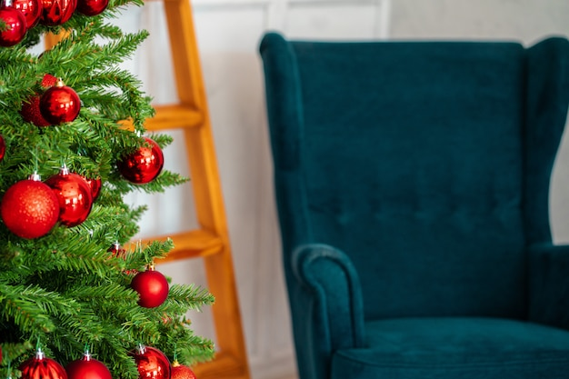 Holiday interior, beautiful decorated christmas tree with blue armchair