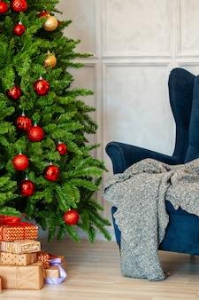 休日のインテリア。青い肘掛け椅子と美しい装飾が施されたクリスマスツリー