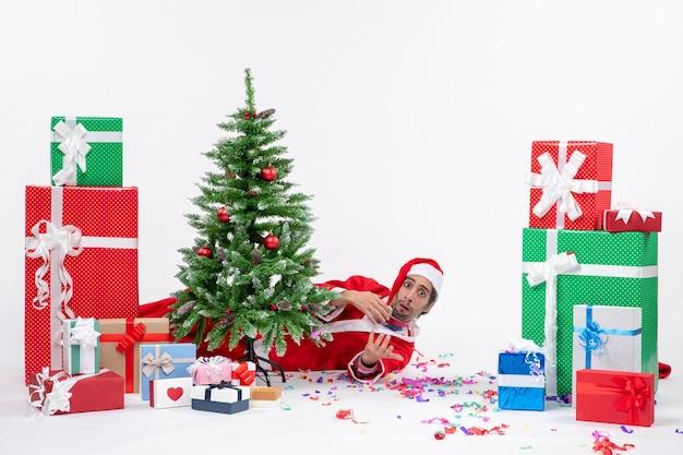 Atmosfera di vacanza con babbo natale che giace dietro l'albero di natale vicino a regali su sfondo bianco