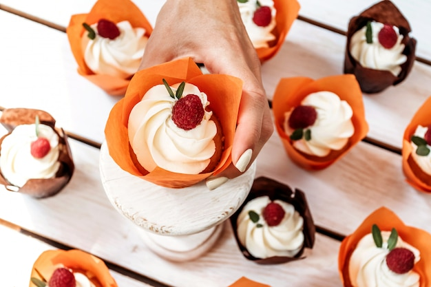 Holiday muffins with cream and berries in individual orange paper packaging