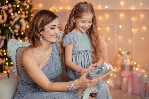 休日新年幸せな母と娘は贈り物を交換します