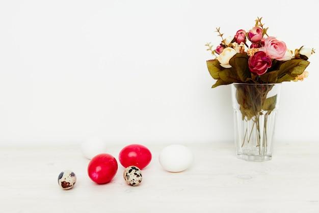 밝은 부활절의 휴일과 꽃병에 꽃의 꽃다발 테이블에 그려진 계란