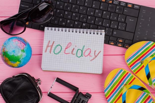 ピンクのテーブルトップに女性の旅行者アクセサリーメガネ財布とフリップフロップとノートブックの休日...