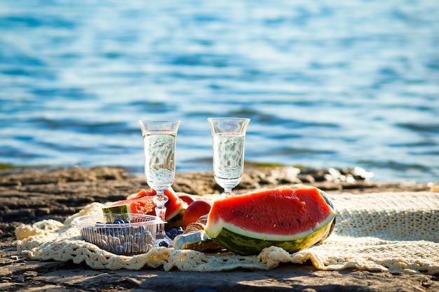 海での休日のピクニックシャンパン、ブルーベリー、スイカ、クロワッサンの2つのグラス