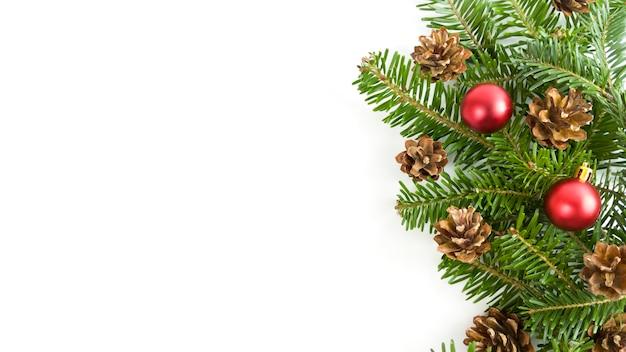 Праздничная открытка с еловыми ветками, шишками и красными шарами на белом фоне. рождественский баннер с копией пространства.