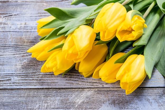 Праздничная открытка с цветами тюльпана на красочном деревянном фоне