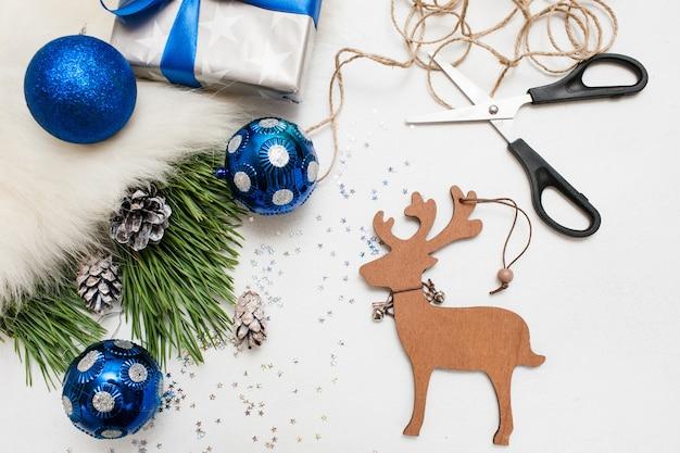 休日の準備。クリスマスと新年。飾りの青いボール、ギフトボックス、松の枝が机の上に置かれている手作りの木製の鹿、コピースペースのある上面図。家とレストランの装飾の概念