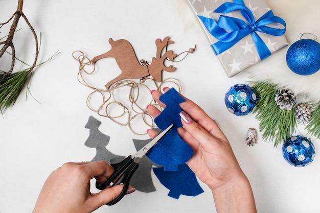 Подготовка к празднику. рождество и новый год. до неузнаваемости женщина ножницами войлочную ель. орнамент шары, подарочная коробка и деревянный олень на столе, вид сверху. концепция украшения дома и ресторана