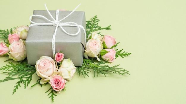 ホリデープレゼント。緑のテーブルにシルバーのギフトボックス。花と葉の装飾