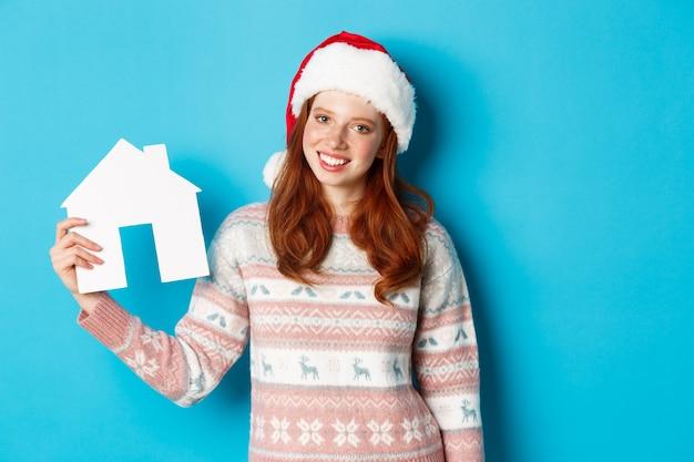 休日のプロモーションと不動産のコンセプト。手に紙の家を持って、青い背景のセーターに立って笑っているサンタ帽子の陽気な赤毛の女性。