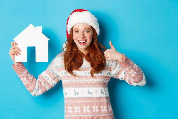 Holiday promos and real estate concept. satisfied female model with red wavy hair, wearing santa hat and sweater, showing paper house model and thumbs-up, blue background