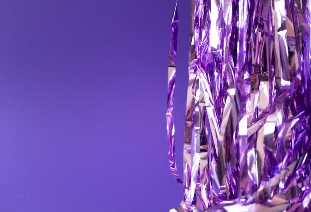 Праздничная фиолетовая мишура на фиолетовом фоне, горизонтальная. творческий фон
