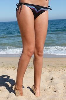 Праздник, курорт, концепция туризма - красивая, привлекательная женщина в черном бикини. молодая и спортивная девушка позирует на пляже летом.