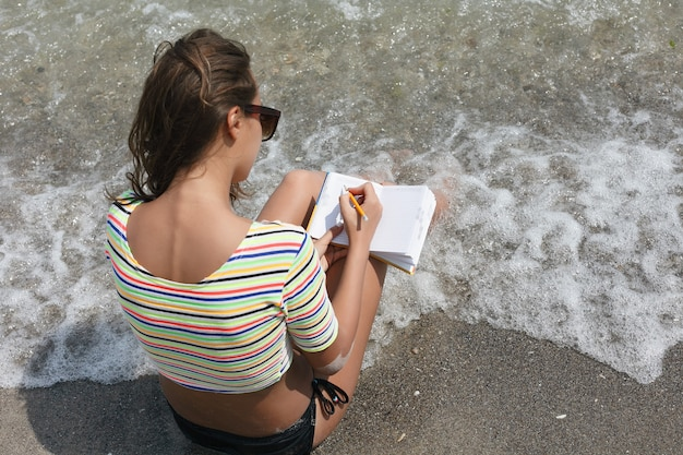 휴일, 리조트, 관광 개념 - 여성은 메모를 하고 해변에 앉아 있습니다. 여자는 일기에 쓰고 모래에 누워