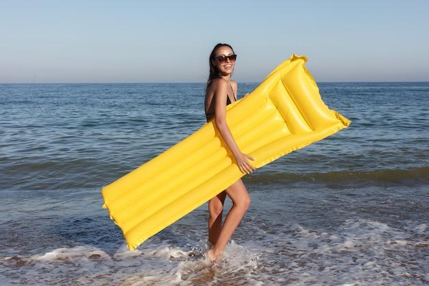 休日、リゾート、観光の概念-夏の晴れた日にビーチで膨脹可能なドーナツと一緒に泳ぐ女性