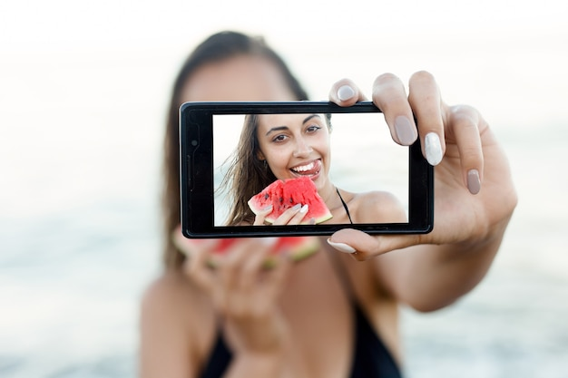休日、リゾート、観光のコンセプト-砂浜で新鮮なスイカを食べる少女。青空に対して休暇中に自分のselfies写真を撮るスマートフォンデバイスを保持している肖像画のティーンエイジャーの女の子