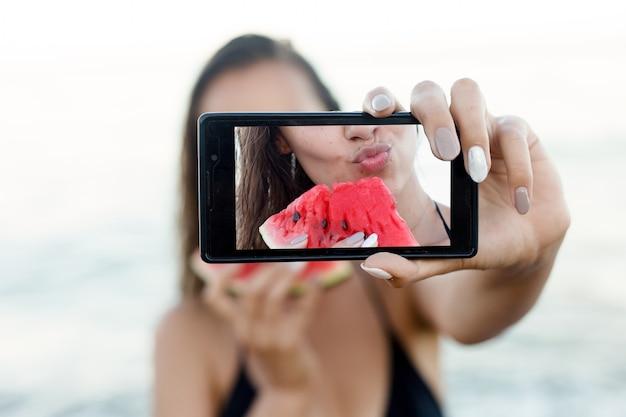 休日、リゾート、観光のコンセプト-砂浜で新鮮なスイカを食べる少女。青い空を背景に休暇中に自分のselfies写真を撮るスマートフォンデバイスを保持している肖像画のティーンエイジャーの女の子