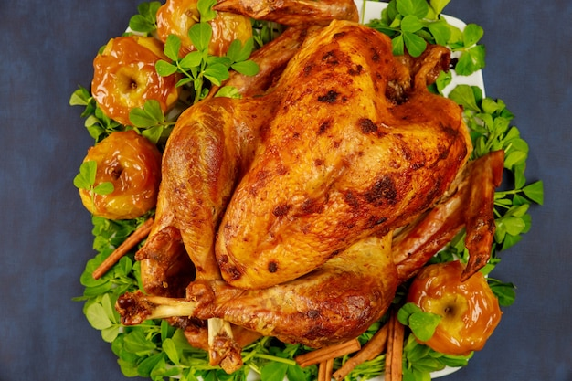 Holiday roasted turkey garnished with caramel apples and clover leaves.
